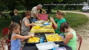 Tradition dictates that the adults cook and cut corn, and the kids bag it.